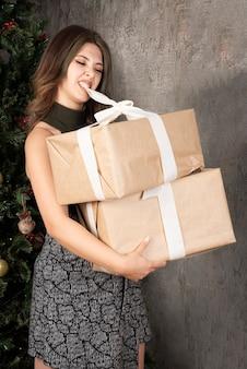 Giovane donna che cerca di aprire i regali di natale con la bocca