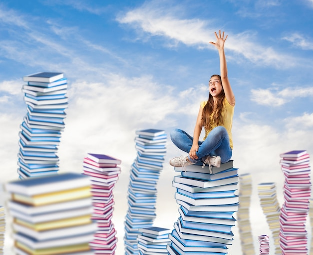 Young woman trying to reach something sitting on a books tower
