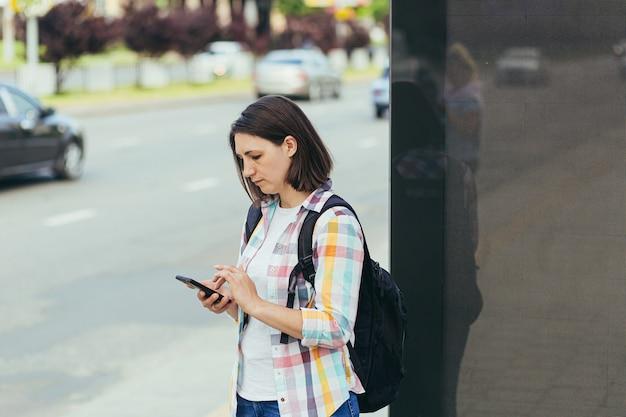 휴대전화의 앱을 사용하여 버스 정류장에서 택시를 잡으려는 젊은 여성