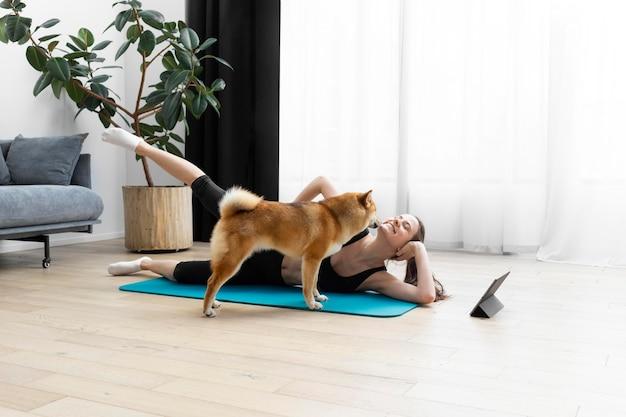 Молодая женщина пытается заниматься спортом рядом со своей собакой