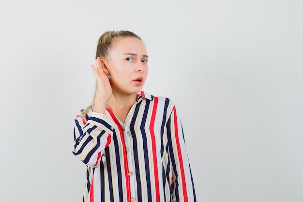 Молодая женщина пытается что-то услышать в полосатой блузке и выглядит любопытной и удивленной