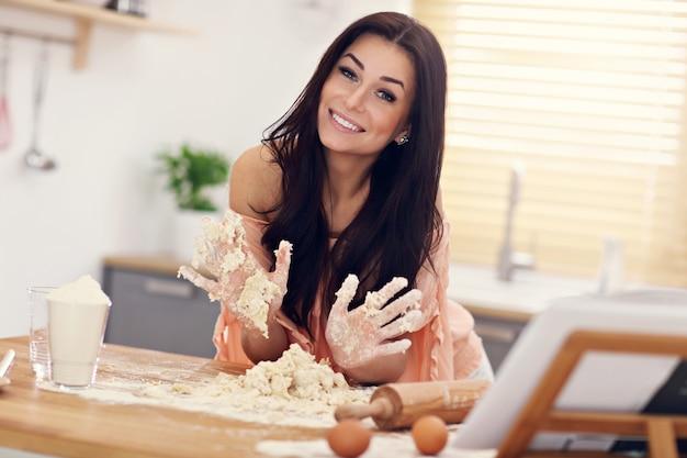 Молодая женщина пытается приготовить вареники на кухне