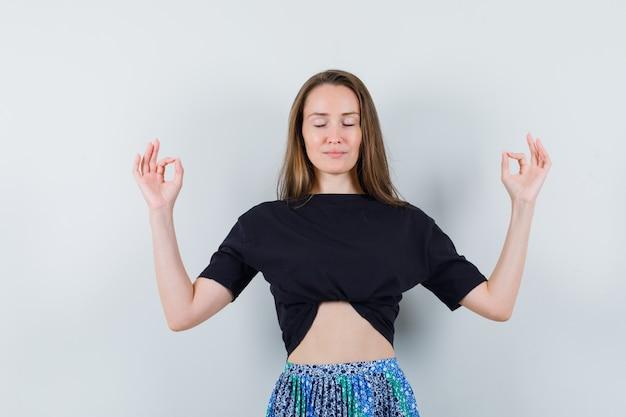 Молодая женщина пытается медитировать в черной футболке и синей юбке и выглядит расслабленной