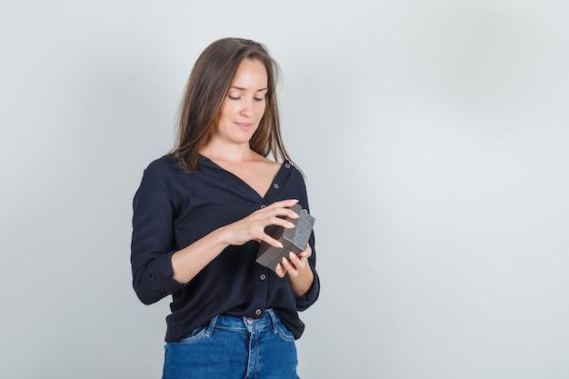 黒のシャツで時計ボックスを開こうとしている若い女性