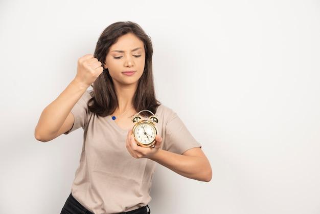 알람 시계를 끄려고하는 젊은 여자.