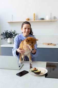 Молодая женщина пытается работать, пока ее собака отвлекает ее