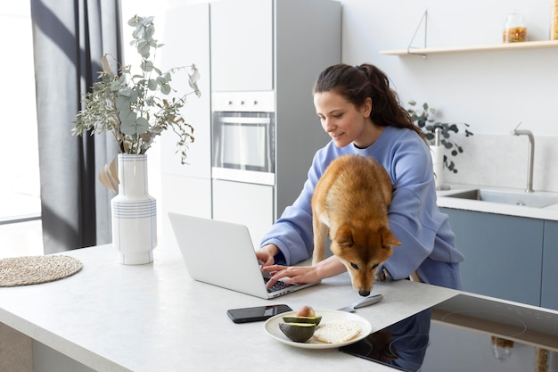 Young woman trying to work while her dog is distracting her