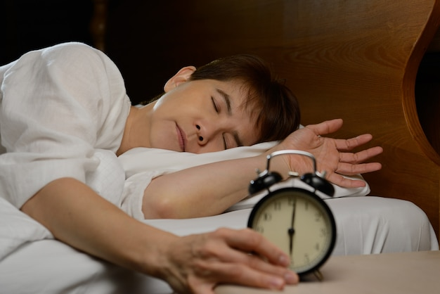Young woman turning off the alarm clock on the bed