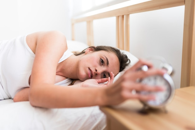 Young woman turning off alarm clock in bedroom