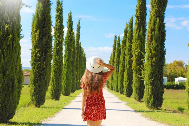 Young woman in tuscan landscape with cypress trees, italy