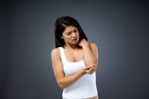 Young woman twisted her arm and holding elbow.