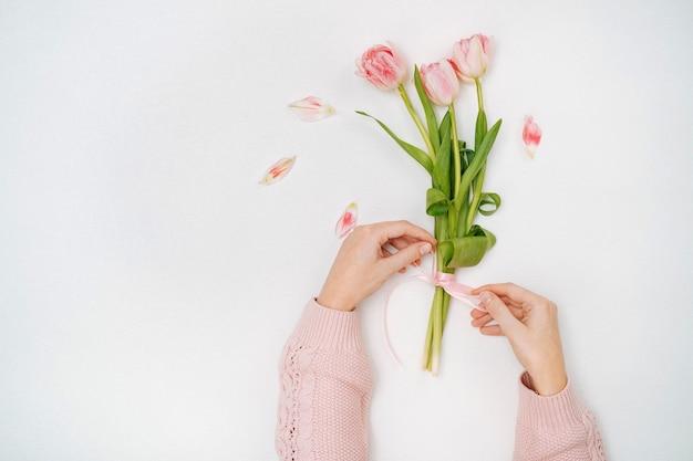 핑크 튤립 꽃다발에 리본을 묶는 젊은 여자. 상위 뷰, 흰색 배경, 텍스트 복사 공간. 3 월 8 일 또는 어머니의 날.