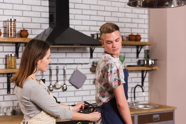 Young woman tying apron of boyfriend