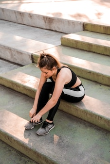 Young woman tying her sneakers