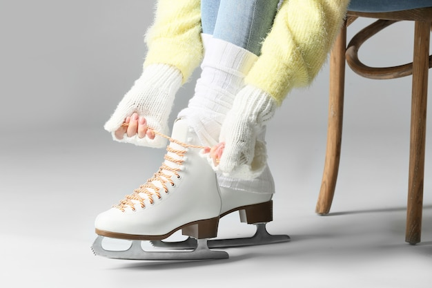 Young woman tying laces on ice skate shoes against grey