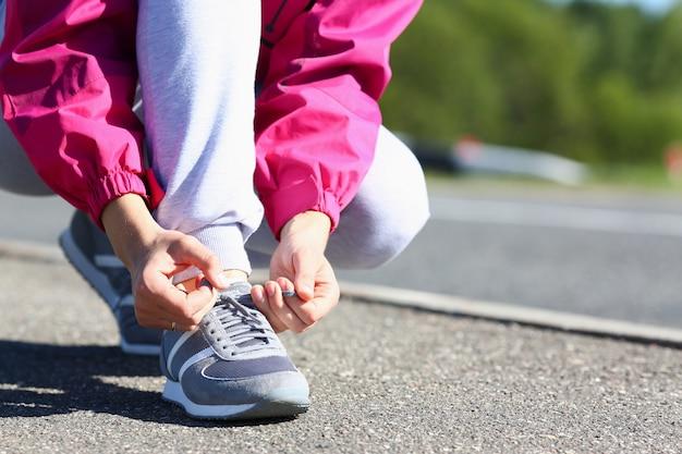 路上で靴ひもを結ぶ若い女性