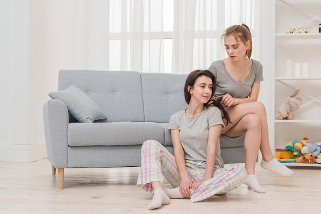若い女性が自宅で彼女のガールフレンドのお下げを結ぶ