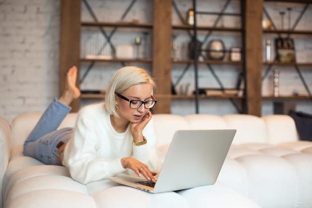 침대에 누워 노트북 컴퓨터에 이메일을 입력하는 젊은 여성, 집에서 비즈니스 파트너에게 답변 보내기