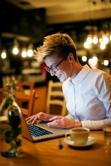 Young woman typing on laptop at cafe. smiling wearing glasses looking at laptop.