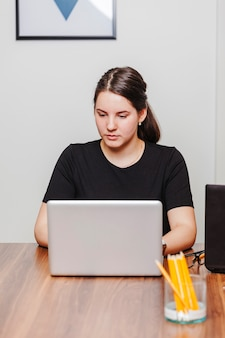 Young woman typing laptop in office