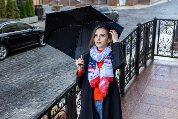 Young woman under an umbrella on a city street