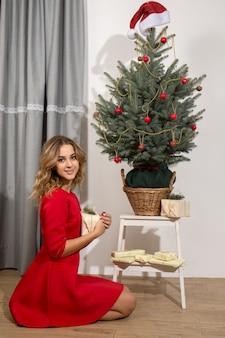 크리스마스 트리 아래 젊은 여자