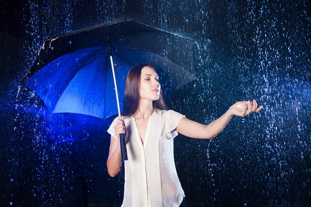 傘の下の若い女性。雨からの保護。雨に触れる
