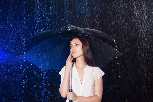 傘の下の若い女性。雨からの保護。