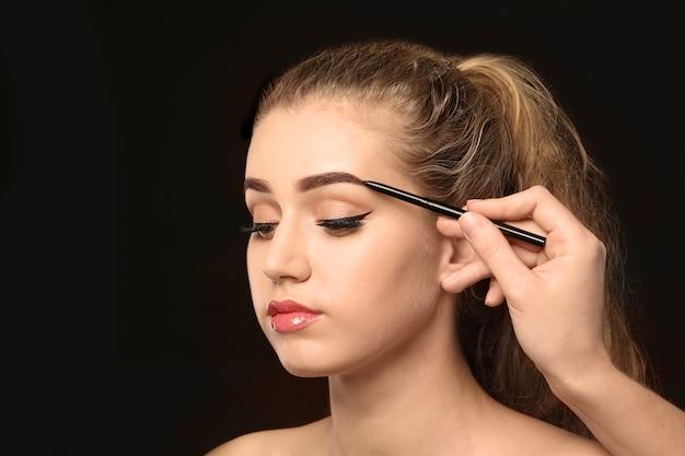 暗闇の中で眉の修正手順を受けている若い女性