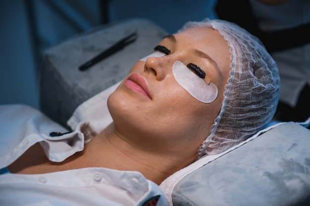 Young woman undergoing eyelash lamination and tinting, closeup