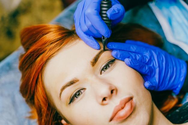 Молодая женщина проходит процедуру перманентного макияжа бровей в тату салоне.
