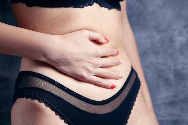 Young woman in underwear holds her hand to her belly