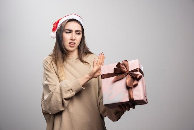 크리스마스 선물에 불만이 젊은 여자.