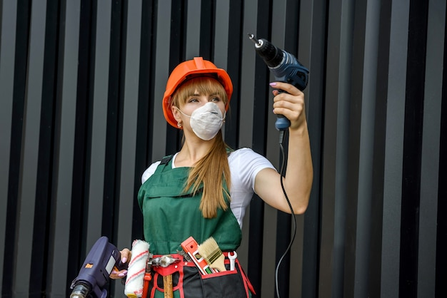 Young woman in uniform and helmet makes repairs with the help of a drill