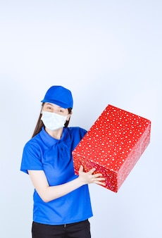 Young woman in uniform and medical mask holding christmas present .