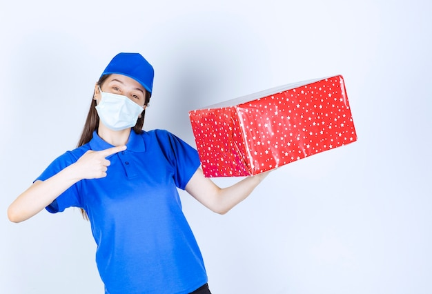Young woman in uniform and medical mask pointing at christmas present .