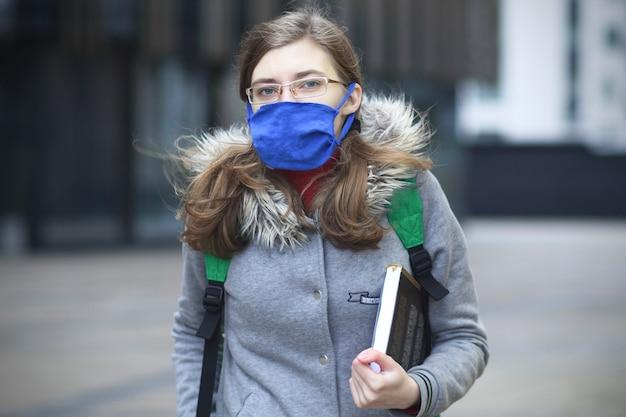 젊은 여자, 대학 또는 대학 학생 소녀 그녀의 얼굴에 보호 마스크와 책, 교과서 및 배낭을 들고 안경에 공부, 수업을하려고합니다. 코로나 바이러스, covid-19, 교육 개념.