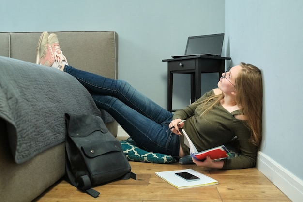 Young woman university student sitting at home on floor and studying using books