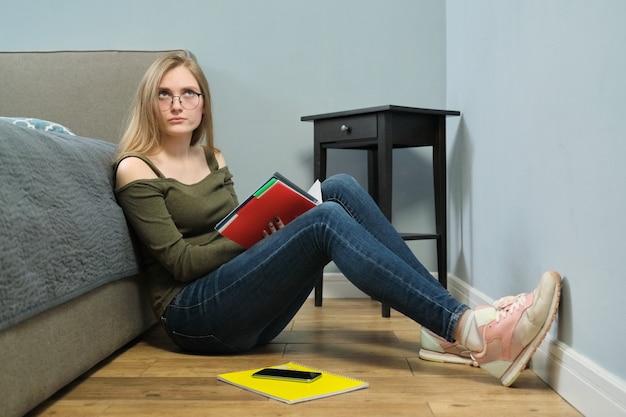 집에서 읽고 공부하는 교과서를 가진 젊은 여자 대학생