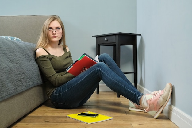 Young woman university student with textbooks reading and studying at home