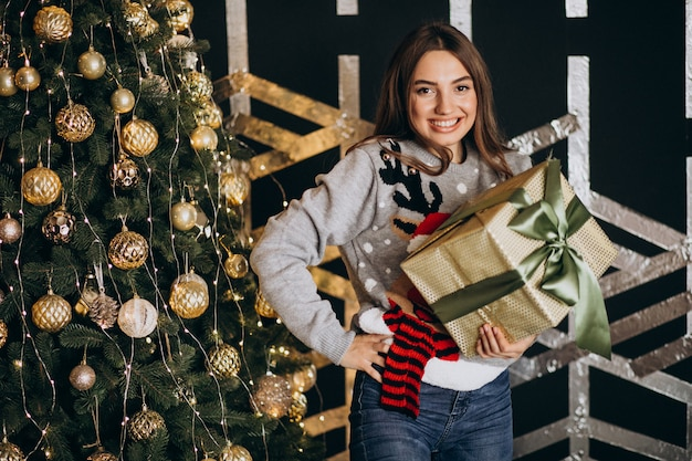 Young woman unpacking christmas present by the christmas tree