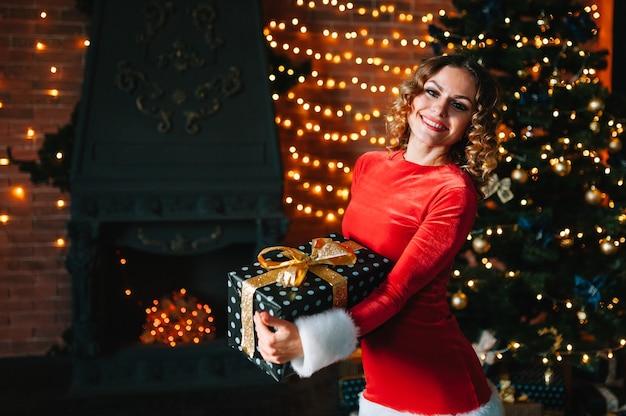 照らされた木の近くでクリスマスプレゼントを開梱する若い女性。クリスマス、新年のお祝いのコンセプト。