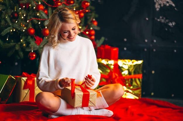 Молодая женщина распаковывает подарки к елке