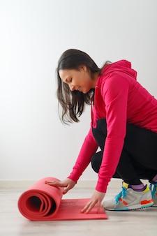젊은 여자는 연습 전에 요가 매트를 펼칩니다.