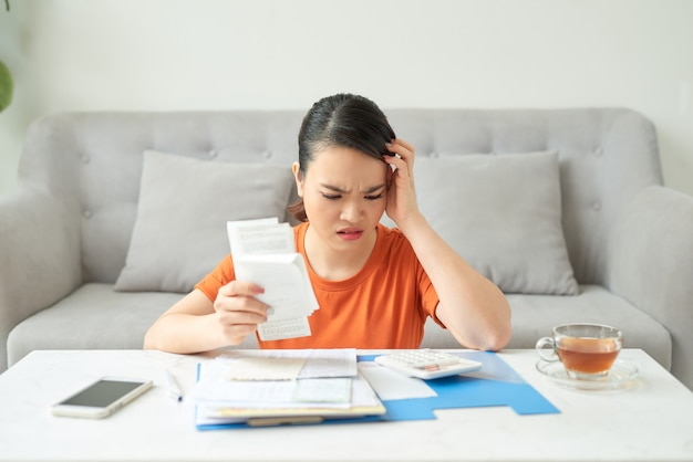 Young woman use calculator analyze charges check utility bills