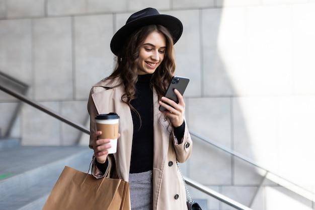 若い女性が携帯電話を使用し、路上で買い物袋を持っています