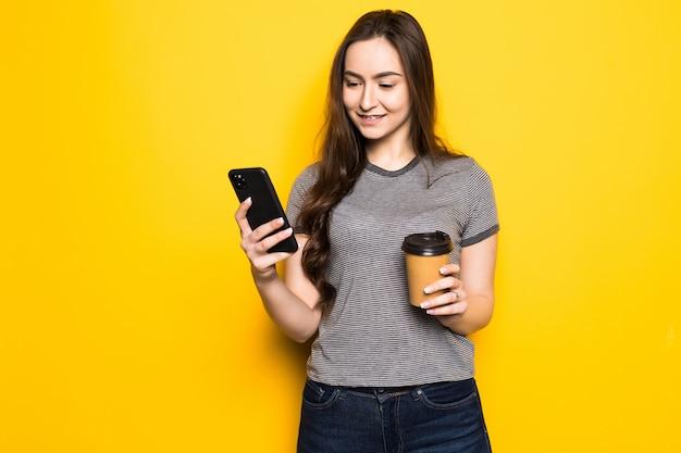 La giovane donna usa il telefono tenendo la tazza di caffè isolata sulla parete gialla