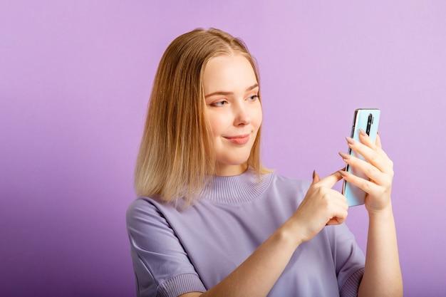 若い女性は、孤立した色の紫色の背景に電話を保持しているスマートフォンを使用してメッセージを送信します。