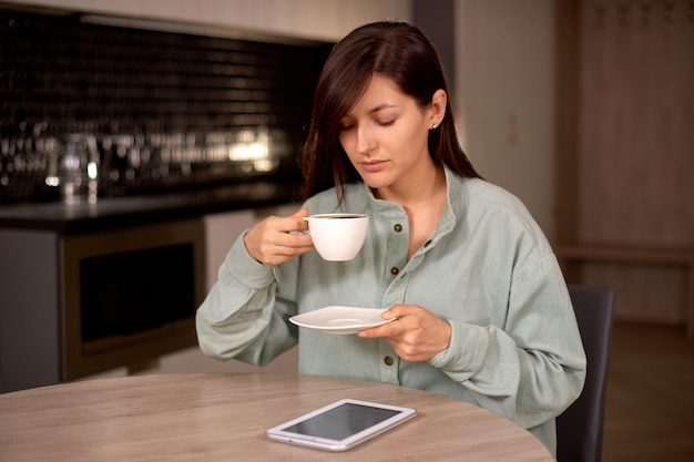 Молодая женщина использует планшет во время отдыха дома с чашкой кофе или чая перед завтраком на кухне