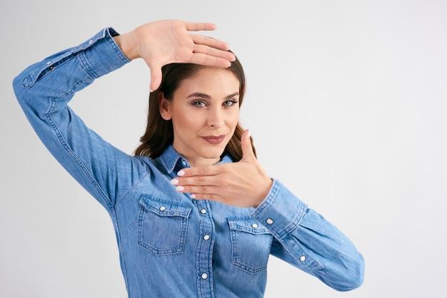 若い女性は彼女の指を使って彼女の顔を組み立てます